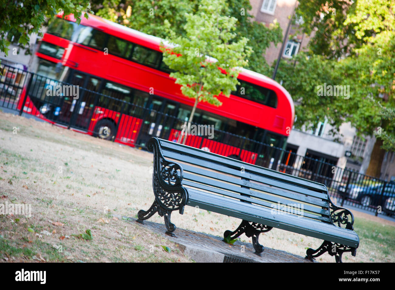 A red double decker bus drives past a park bench in London city - Stock Image