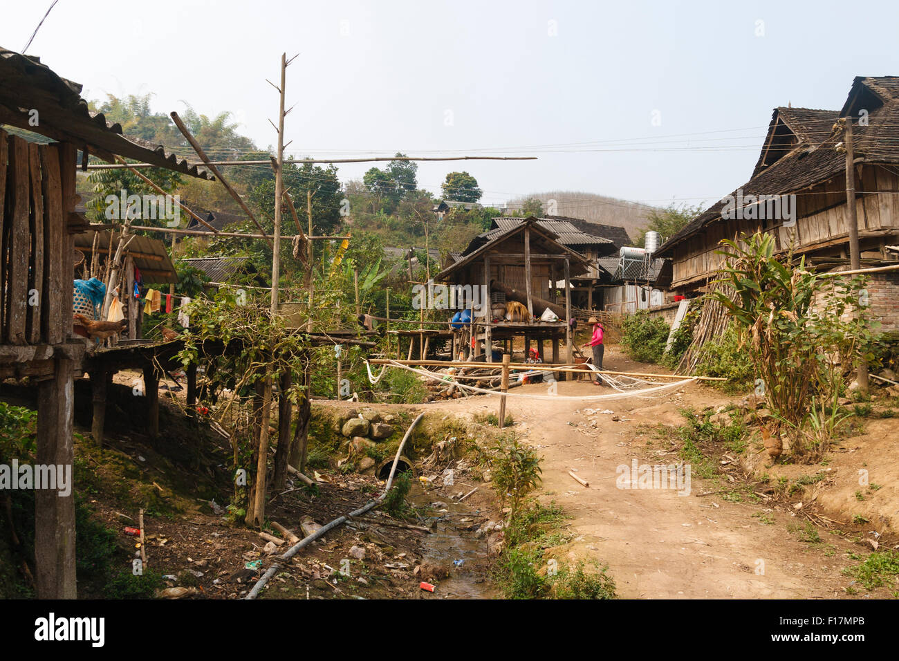 A rural village in Xishuangbanna, Yunnan, China where women are weaving and spinning in traditional fashion - Stock Image