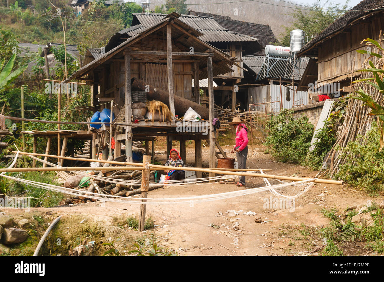 Rural village in Xishuangbanna, Yunnan, China, where women are weaving and spinning in traditional fashion - Stock Image