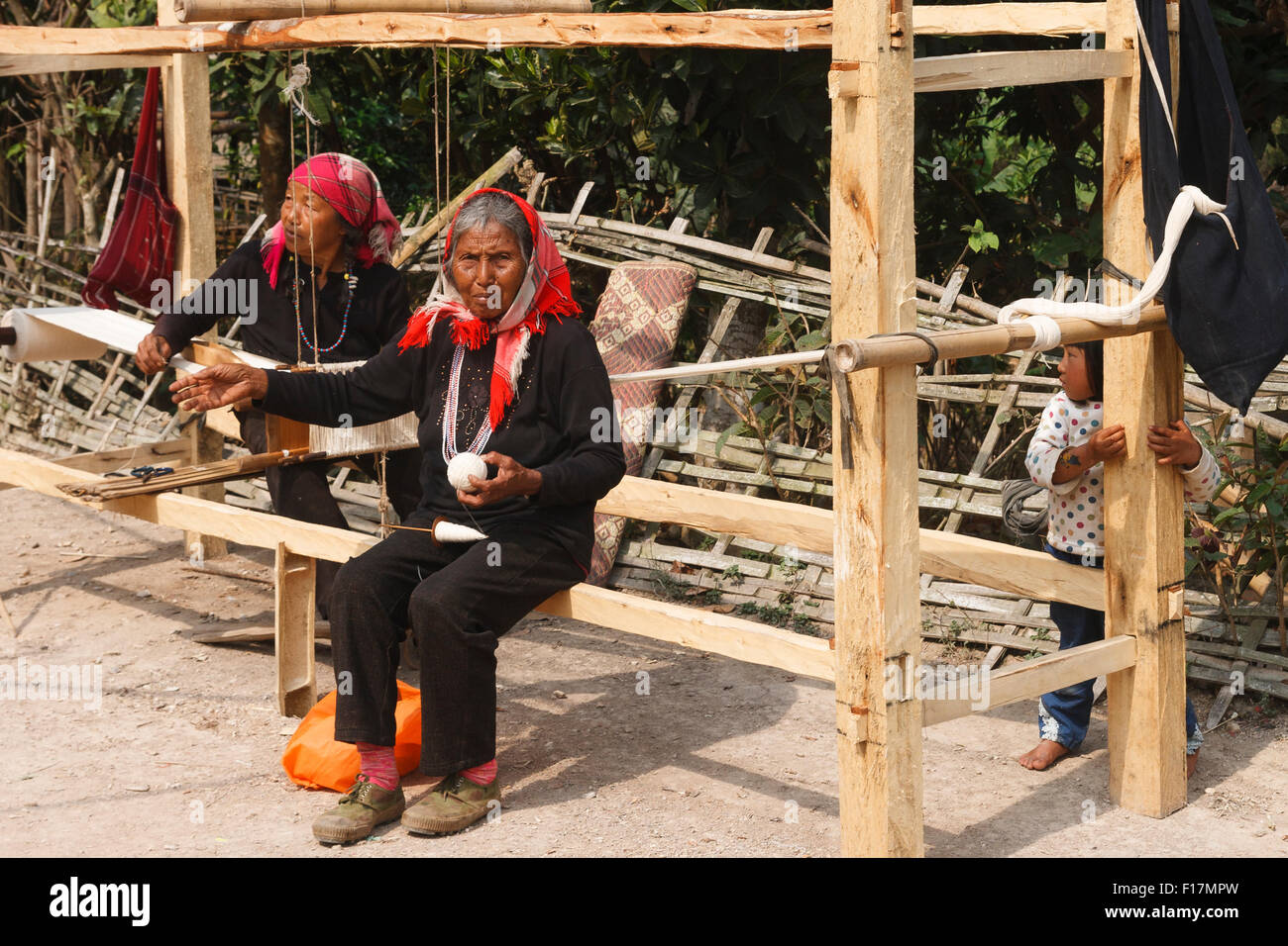 Old Dai women in a rural village in Xishuangbanna, Yunnan, China, weaving using a traditional wooden loom - Stock Image