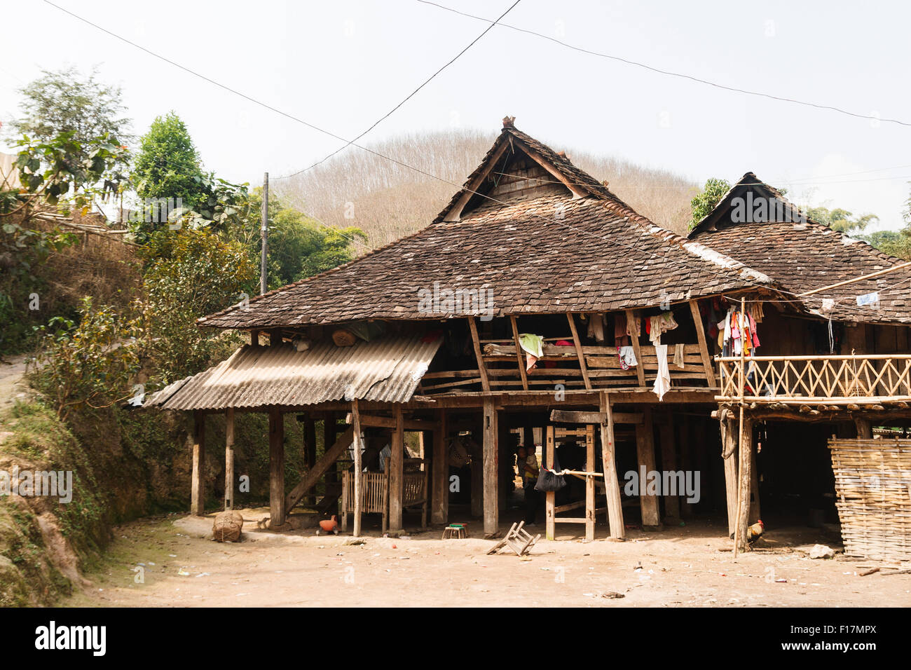 Traditional, rustic, wooden hut house in rural village in Xishuangbanna, Yunnan, China - Stock Image