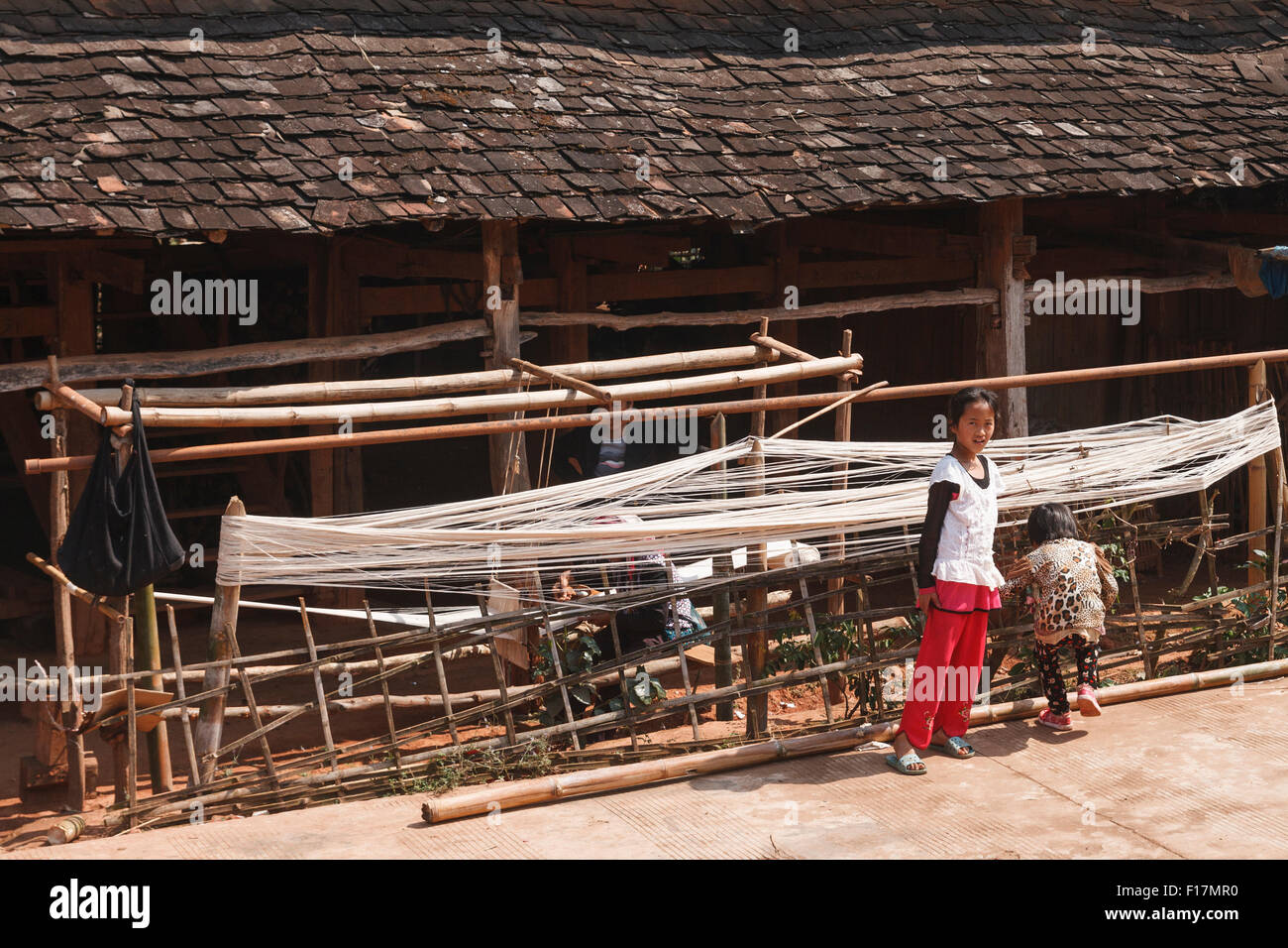 Children in a rural village in Xishuangbanna, Yunnan, China in front of a traditional hut where weaving and spinning - Stock Image