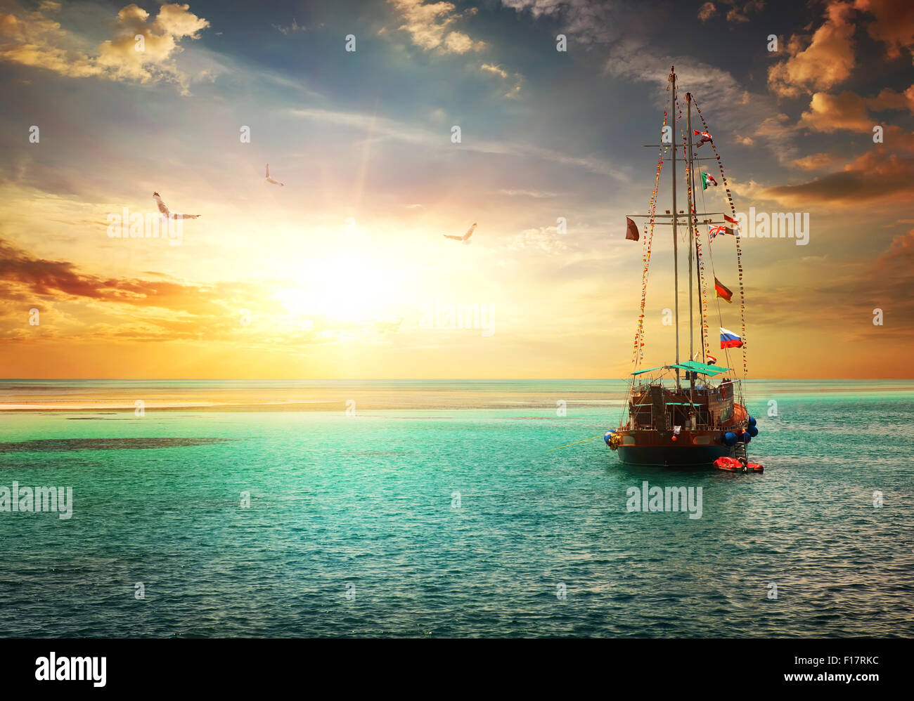 Beautiful sunset over yacht in the sea - Stock Image