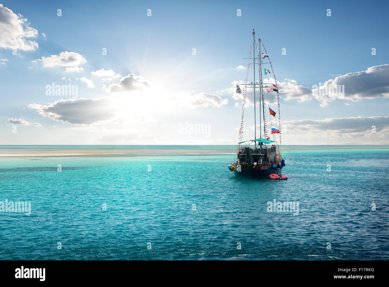 Yacht in the sea near island at sunrise - Stock Image