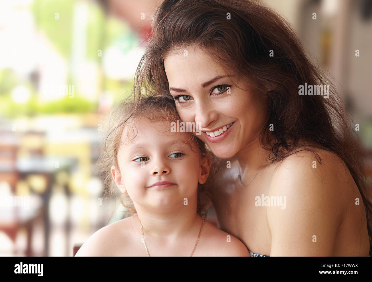 Happy smiling mother cuddling her cute daughter in restaurant. Closeup family portrait - Stock Image
