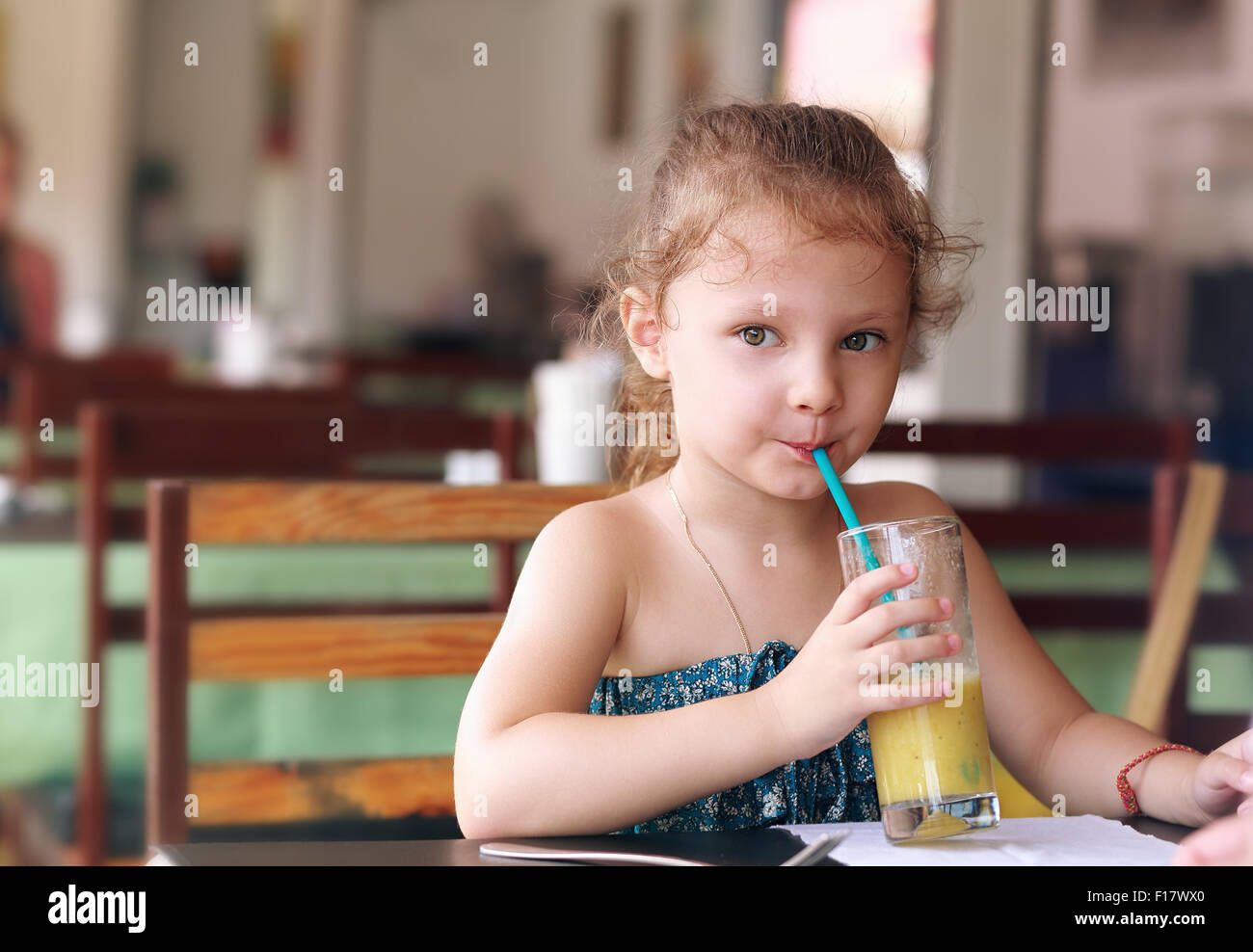 Cute small kid girl drinking juice in cafe with serious look - Stock Image