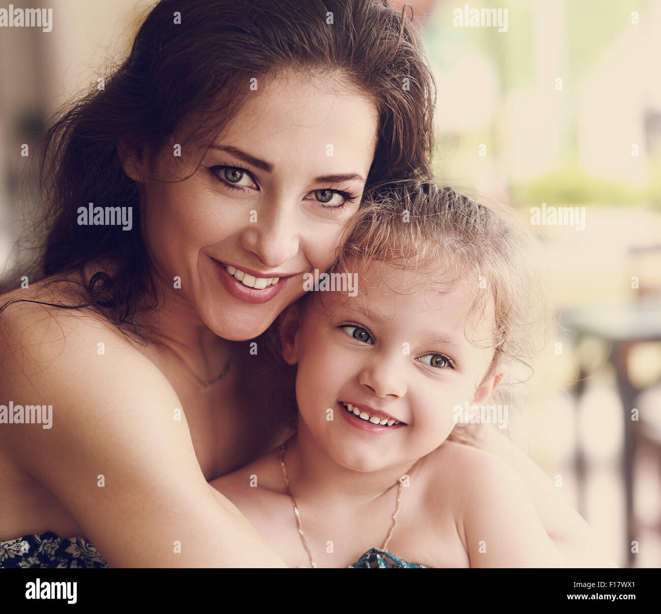 Happy beautiful mother cuddling her small daughter with smile in cafe. Closeup vintage portrait - Stock Image