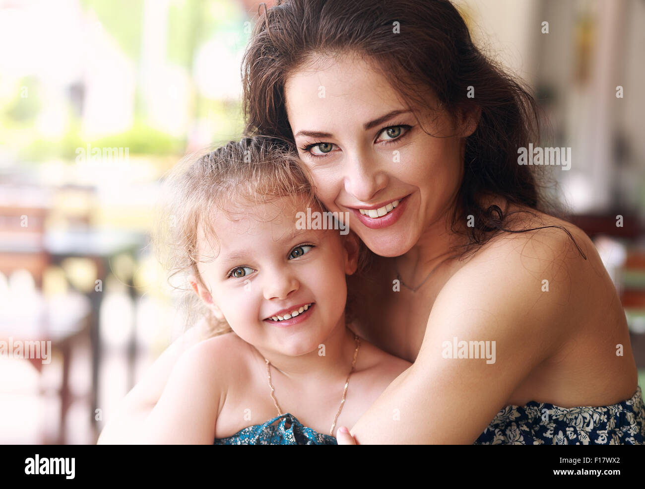 Happy beautiful mother cuddling her daughter with smile in cafe. Closeup portrait - Stock Image