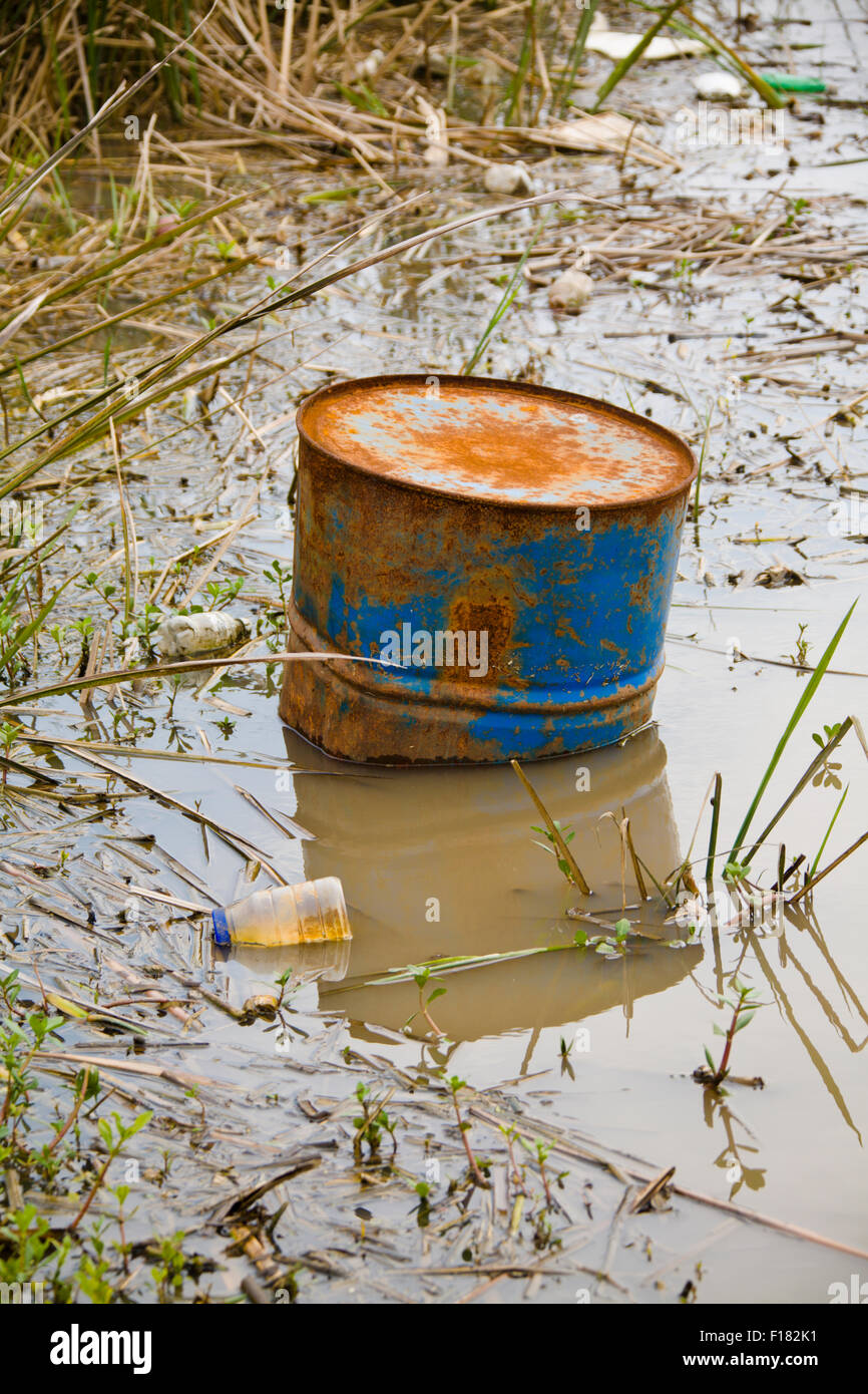 Trash and Toxic waste sitting in a pond of brown water - Stock Image