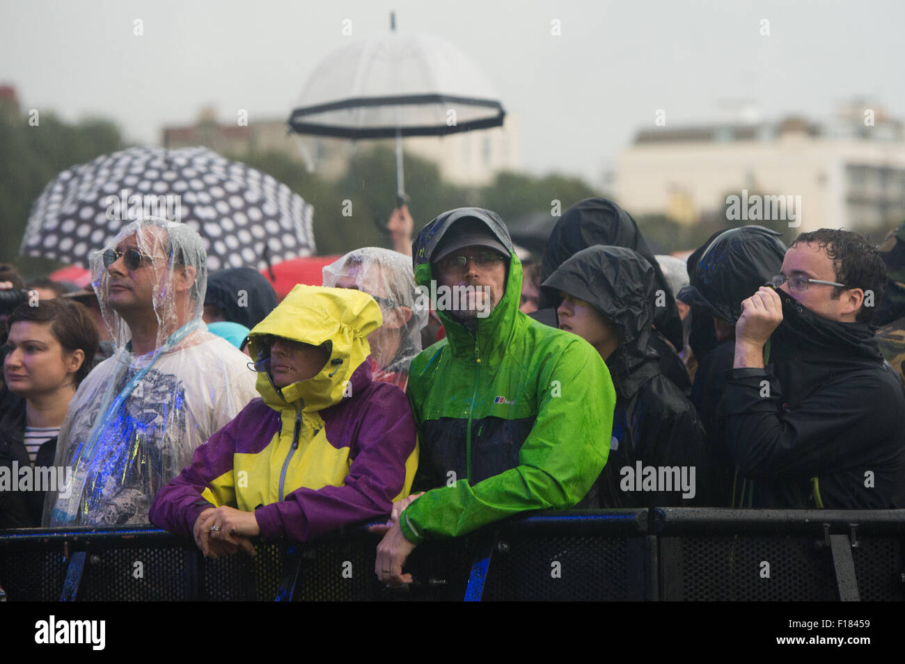 Portsmouth, UK. 29th August 2015. Victorious Festival - Saturday. The crowd shelter from the rain with waterproofs, - Stock Image