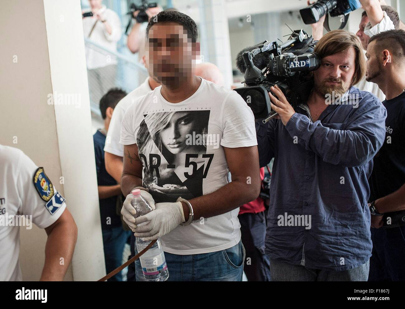Kecskemet, Hungary. 29th Aug, 2015. One of the four suspects is led by the Hungarian police official into a courtroom - Stock Image