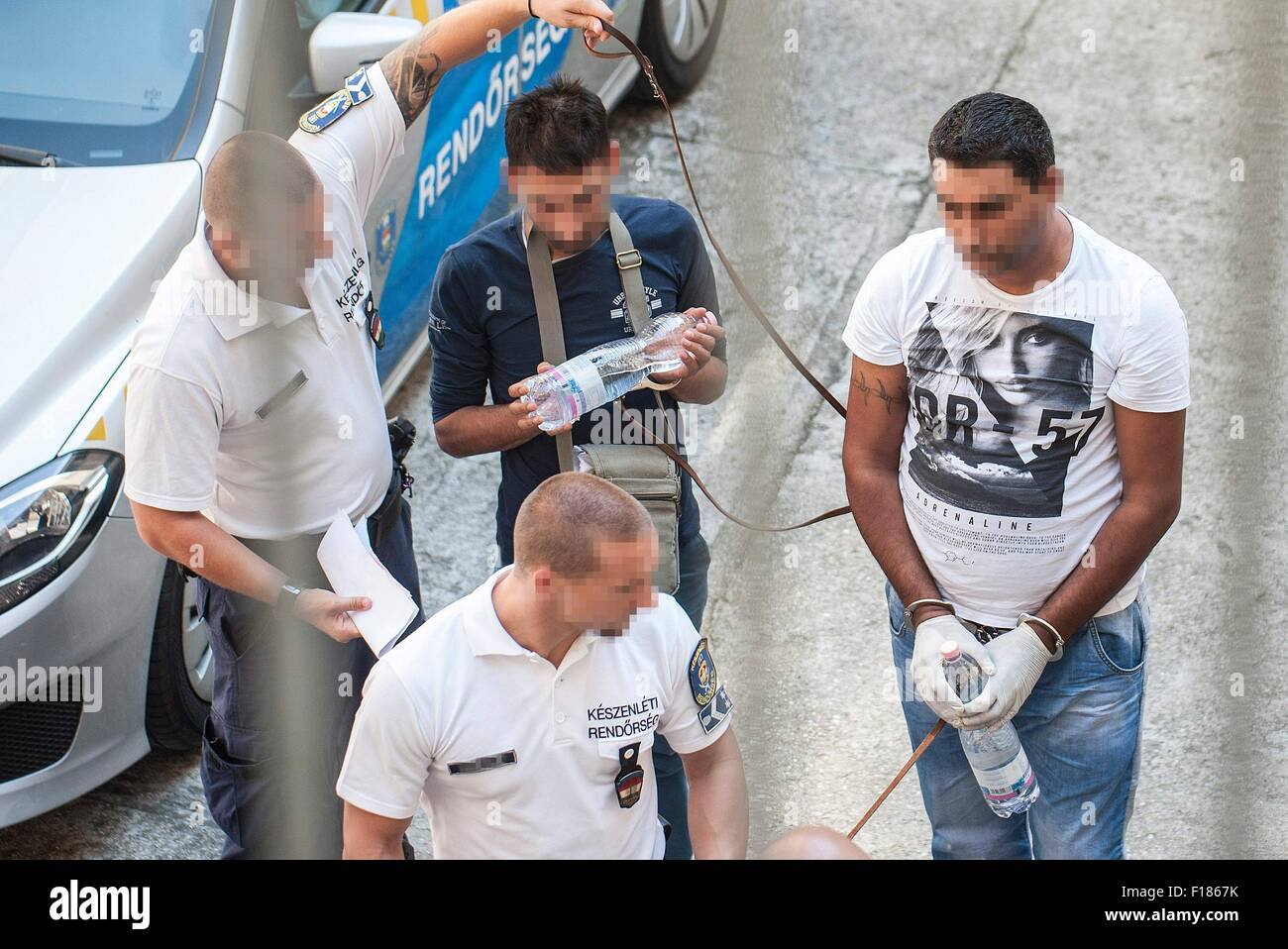 Kecskemet, Hungary. 29th Aug, 2015. Two of the four suspects are led by the Hungarian police official into a courtroom - Stock Image