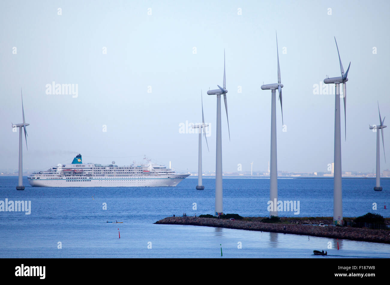 Copenhagen the capital and most populated city of Denmark, wind turbines with cruise ship passing - Stock Image