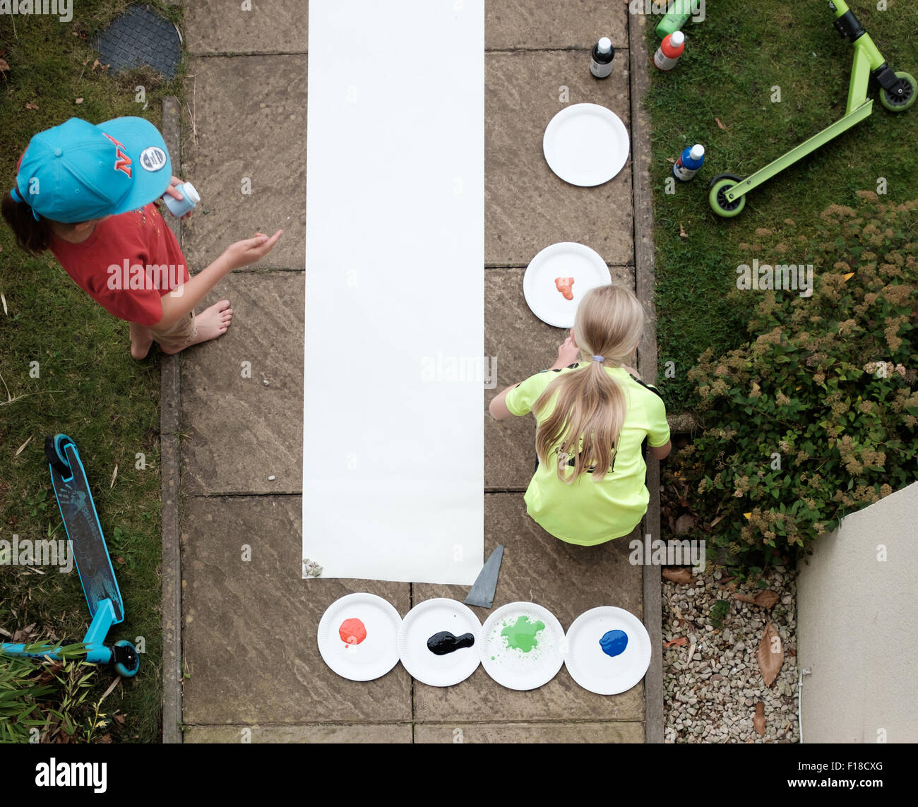 Aerial shot of young girls painting outdoors using scooters with paint on the wheels - Stock Image