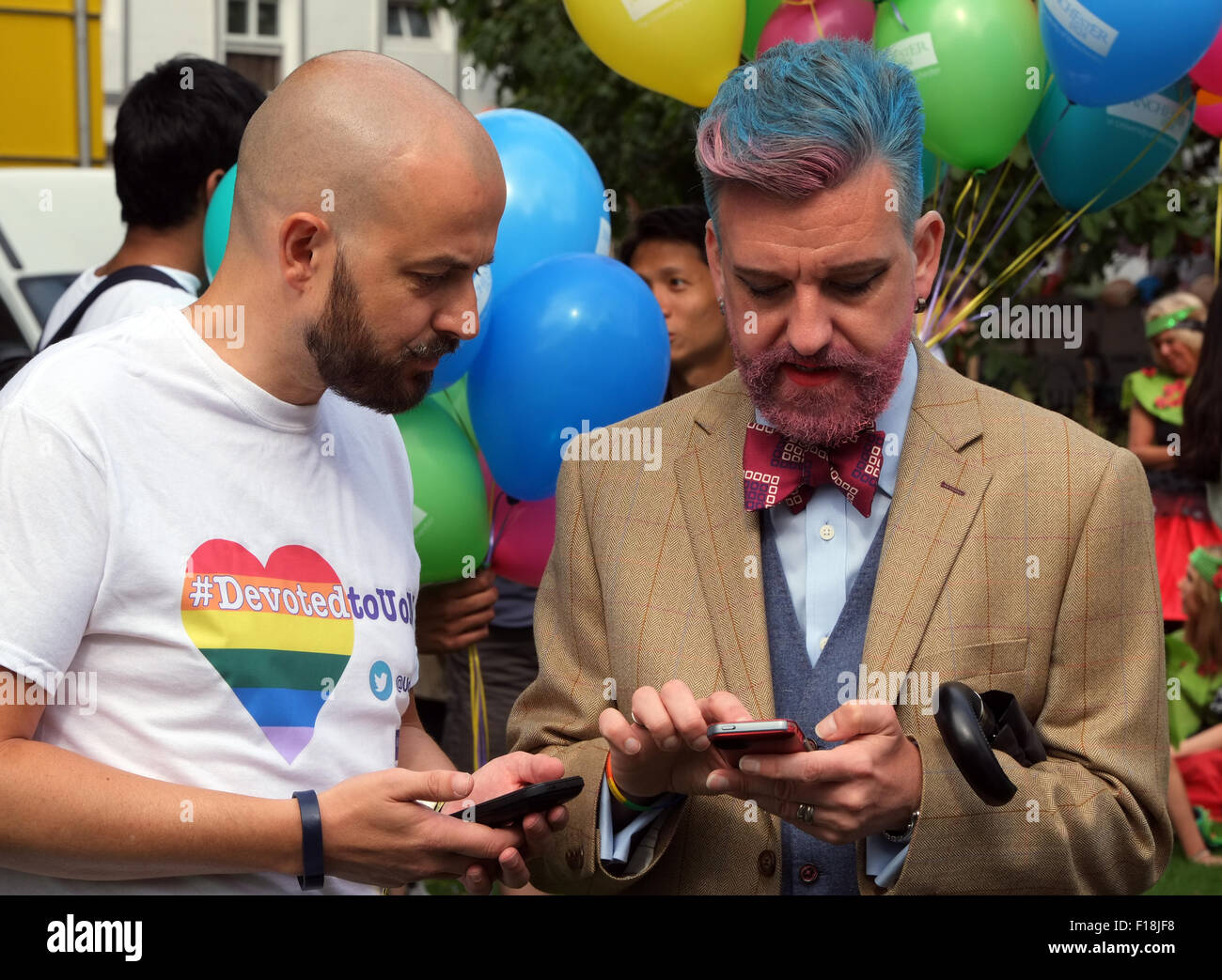 Gay men using their smartphones while preparing for the Manchester Pride 2015 Big Parade through the City Centre - Stock Image