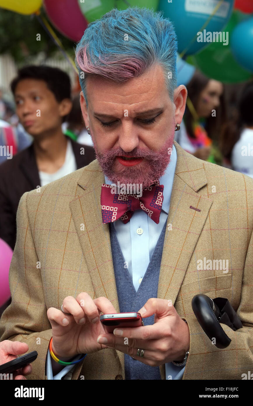 Gay man using his smartphone while preparing for the Manchester Pride 2015 Big Parade through the City Centre - Stock Image