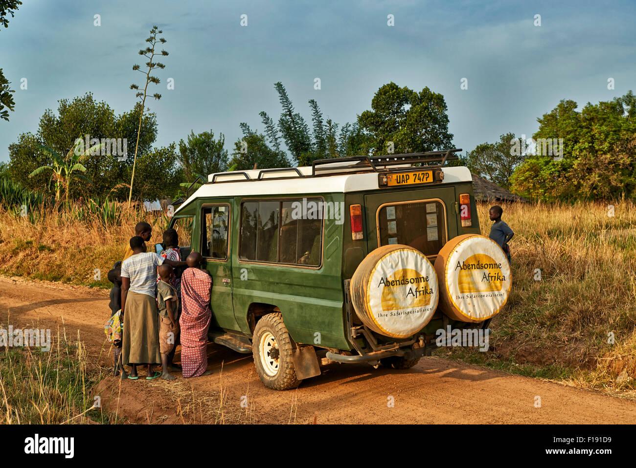 locals around 4x4 in village of Uganda, Africa - Stock Image