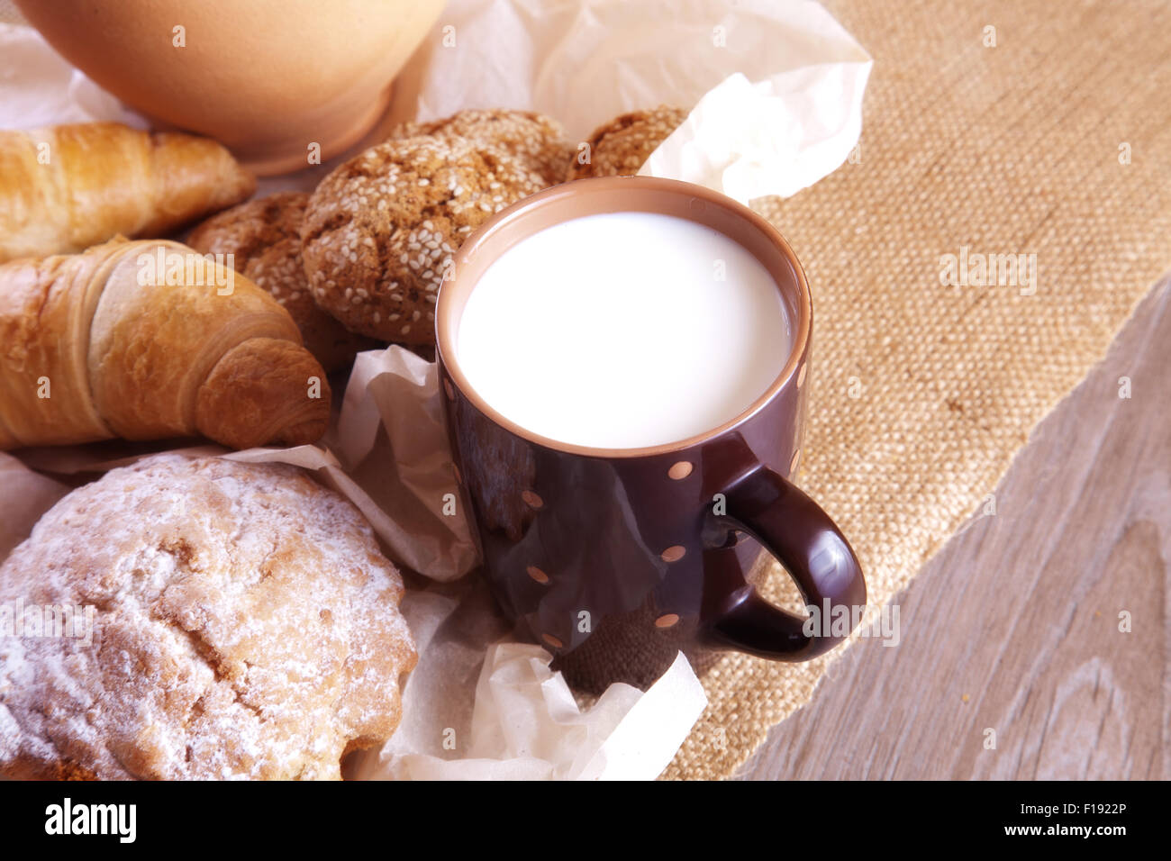 Milk and homemade cakes on a table in rustic style - Stock Image