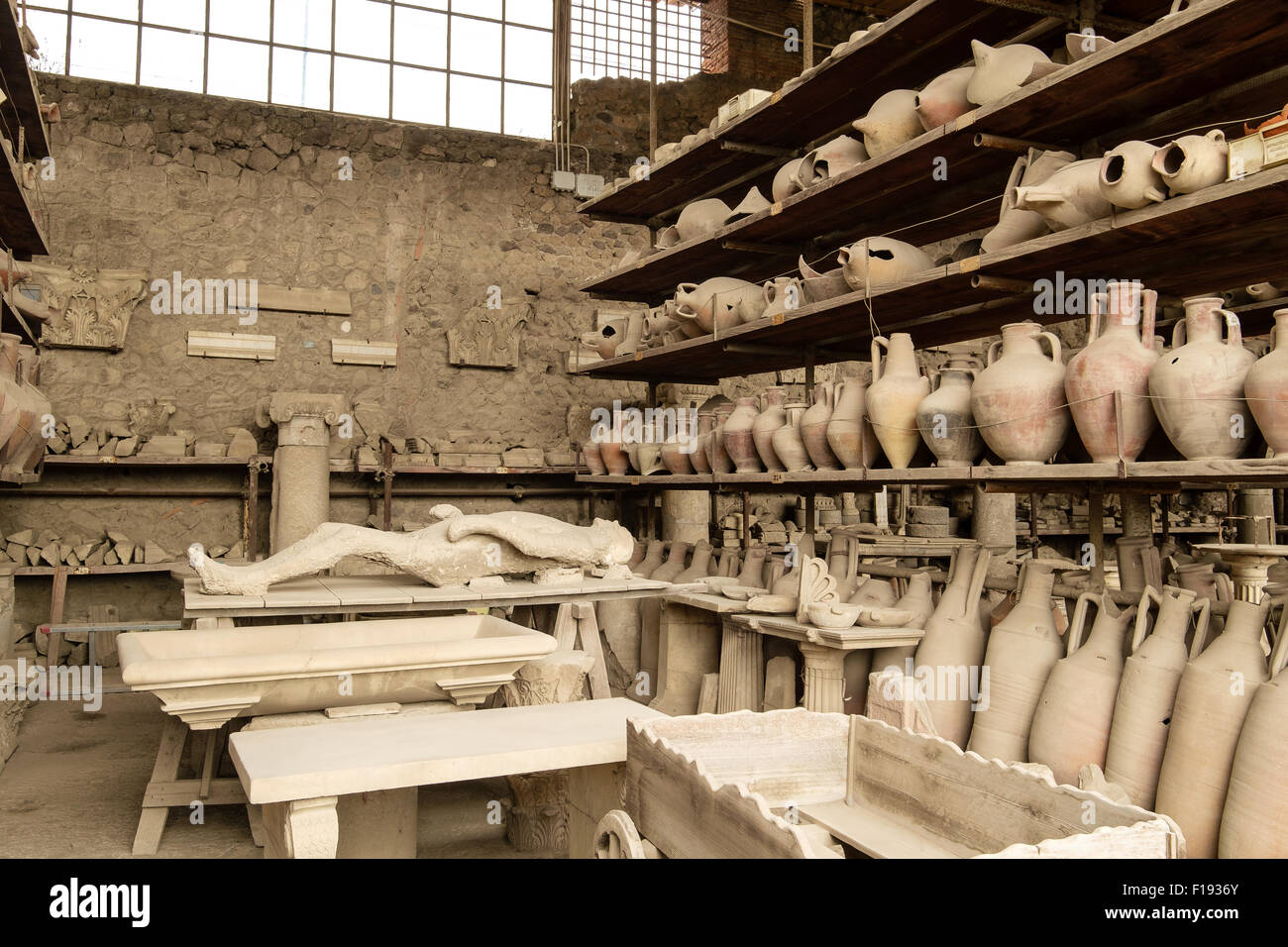 Pots and other artifacts from Pompeii in storage and on display on shelving - Stock Image
