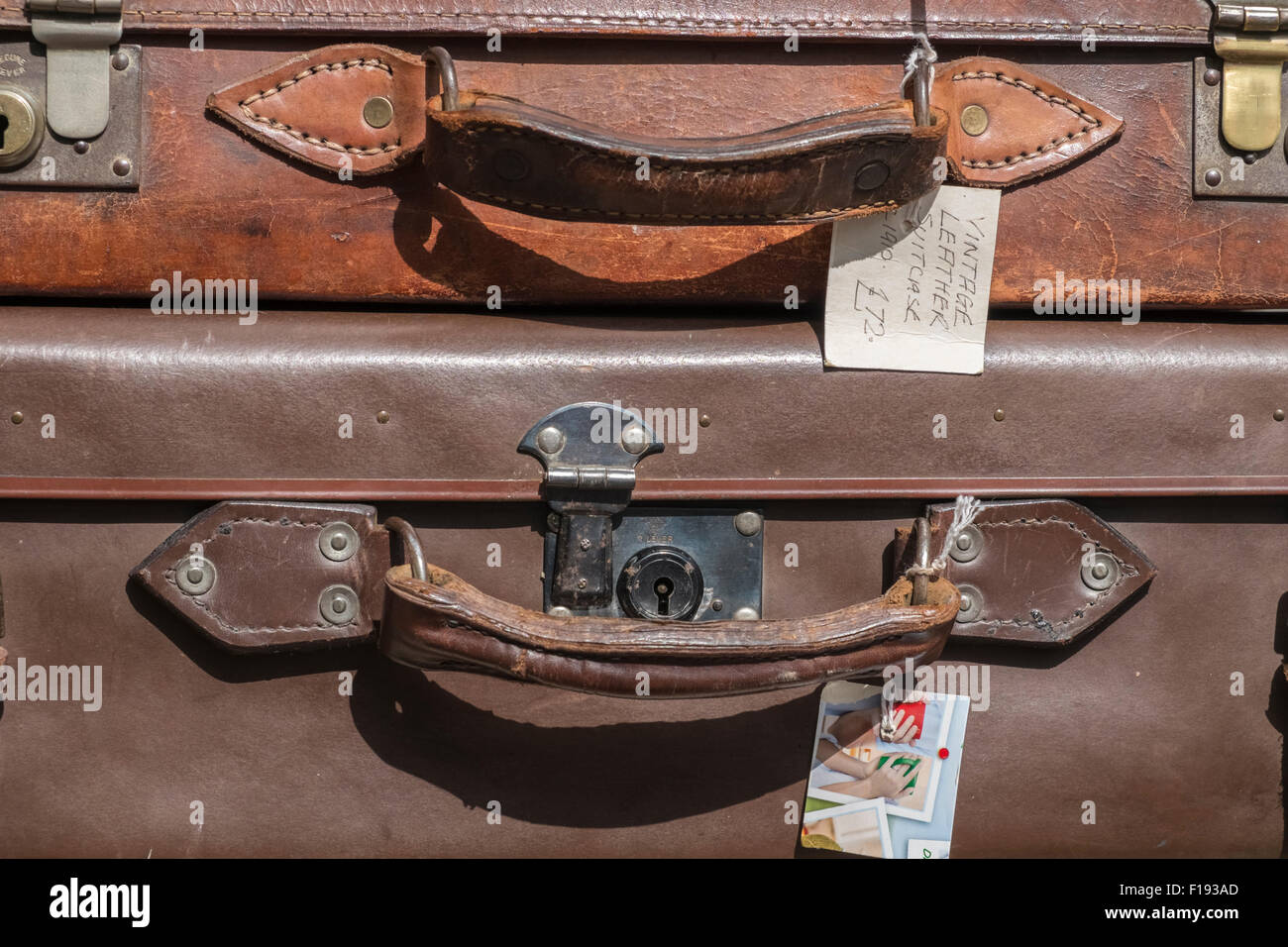 Close up view of two old leather suitcases on display for sale at an antiques store. - Stock Image