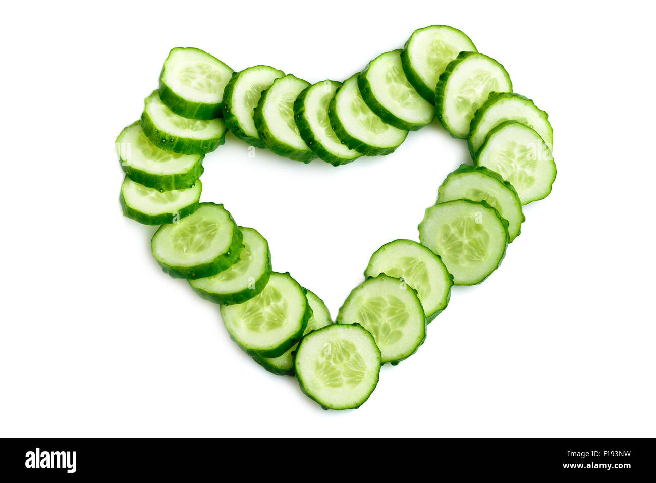 Cucumber slices arranged as heart shape isolated over white background - Stock Image