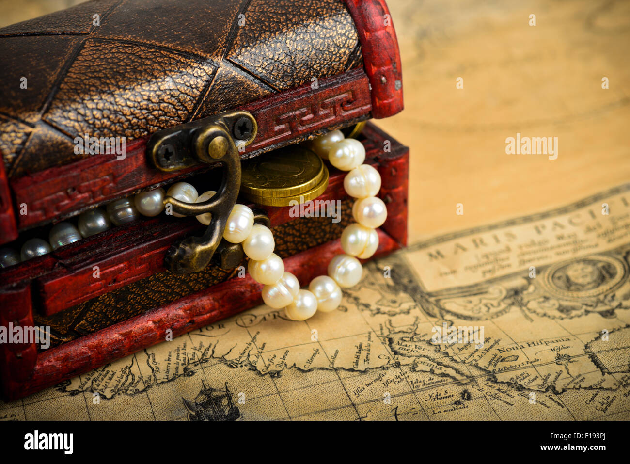 Treasure chest with coins on old adventure maps - Stock Image