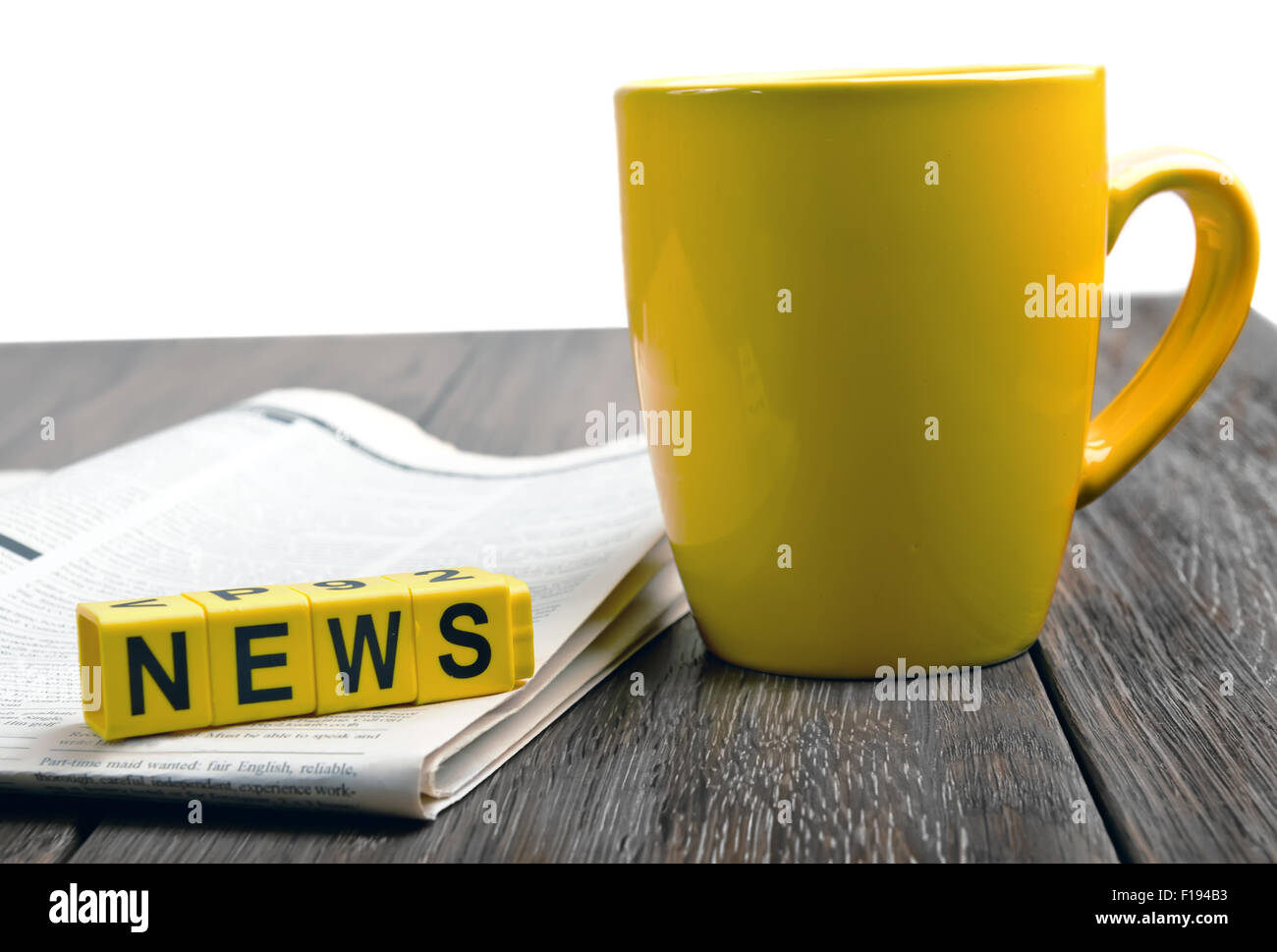newspaper and coffee cup on wooden table - Stock Image