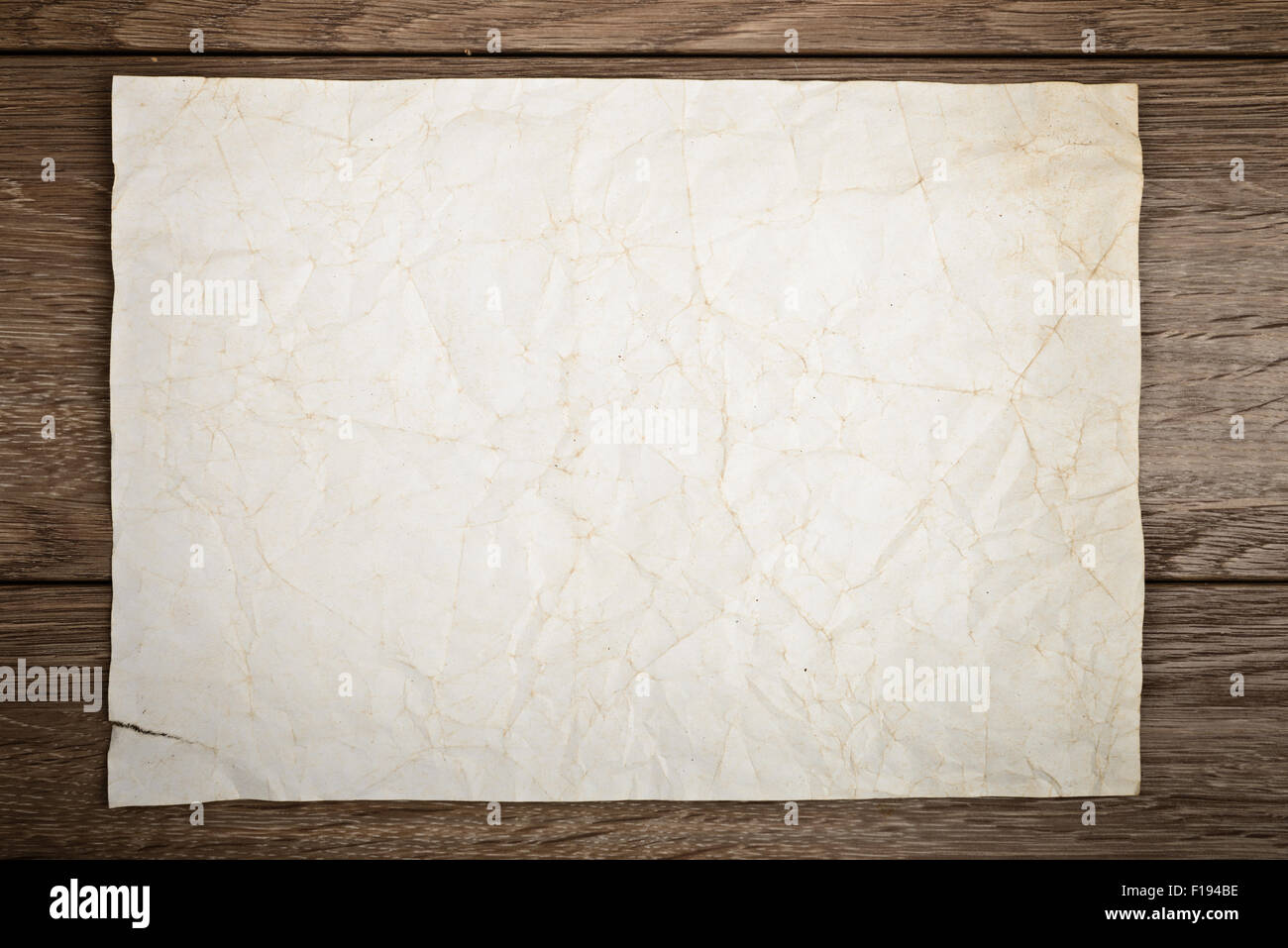 Old paper on wooden table - Stock Image