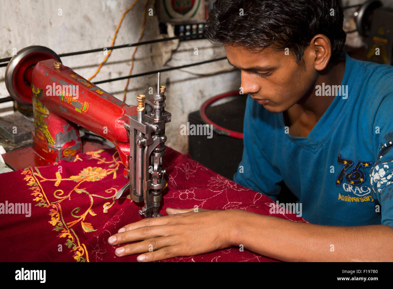 India, Jammu & Kashmir, Srinagar, Old City, crafts, young worker machine embroidering pashmina decoration - Stock Image