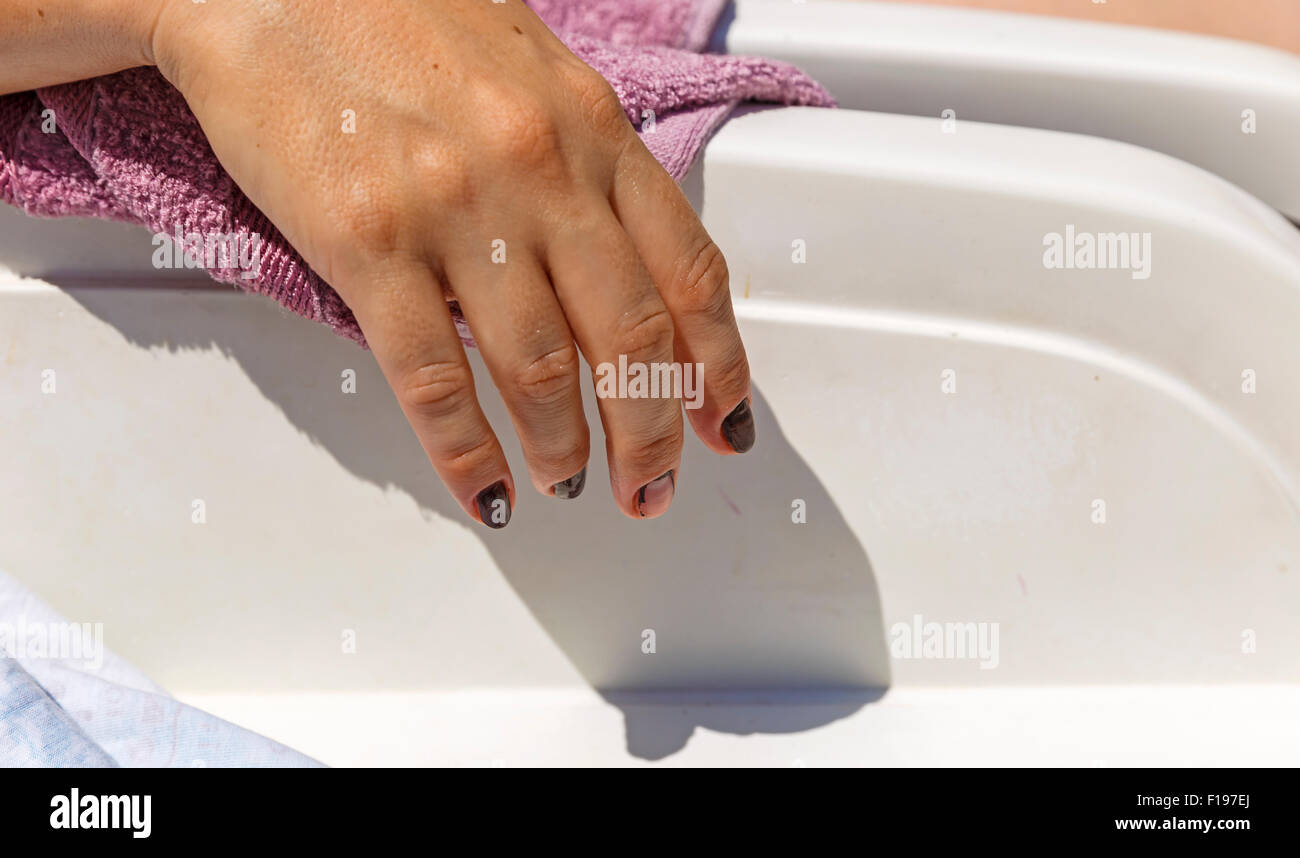 Female hand hanging from couches - Stock Image