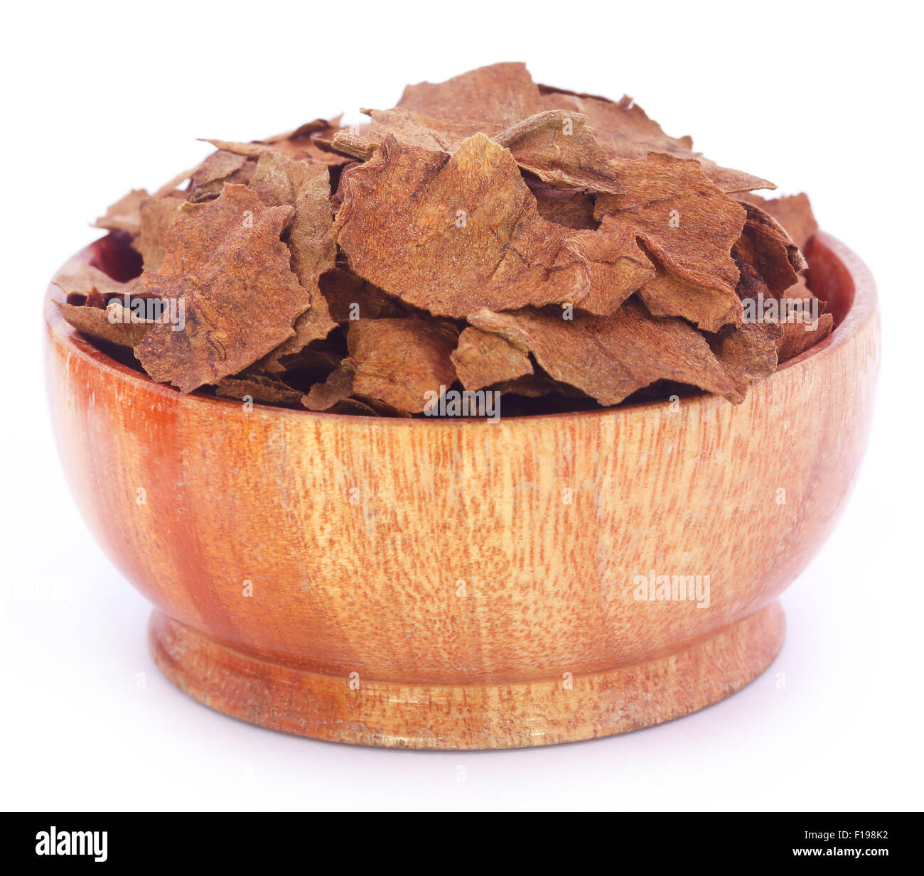 Dry tobacco leaves in a wooden bowl - Stock Image