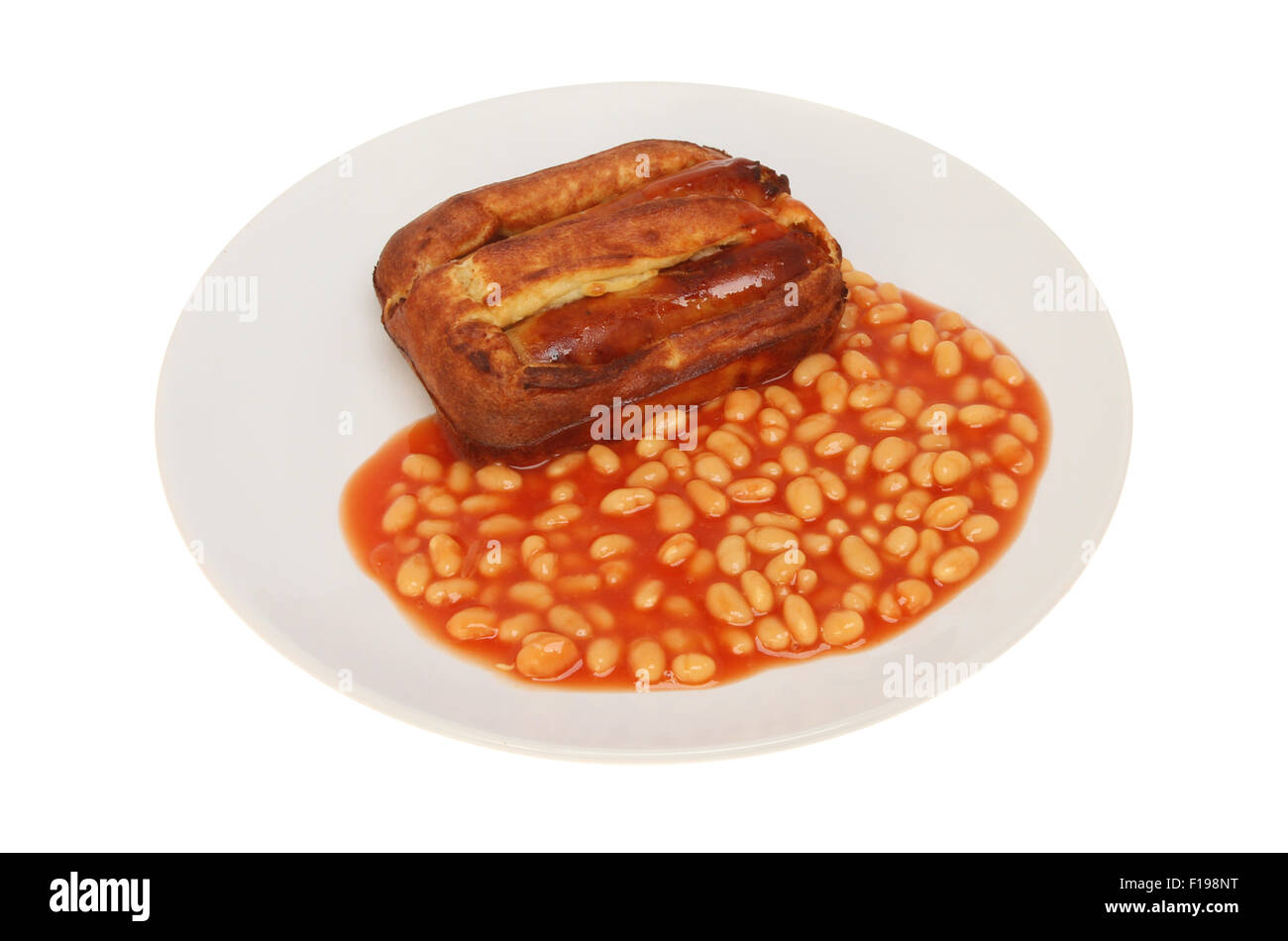 Toad in the hole, sausages baked in batter, with baked beans on a plate isolated against white - Stock Image