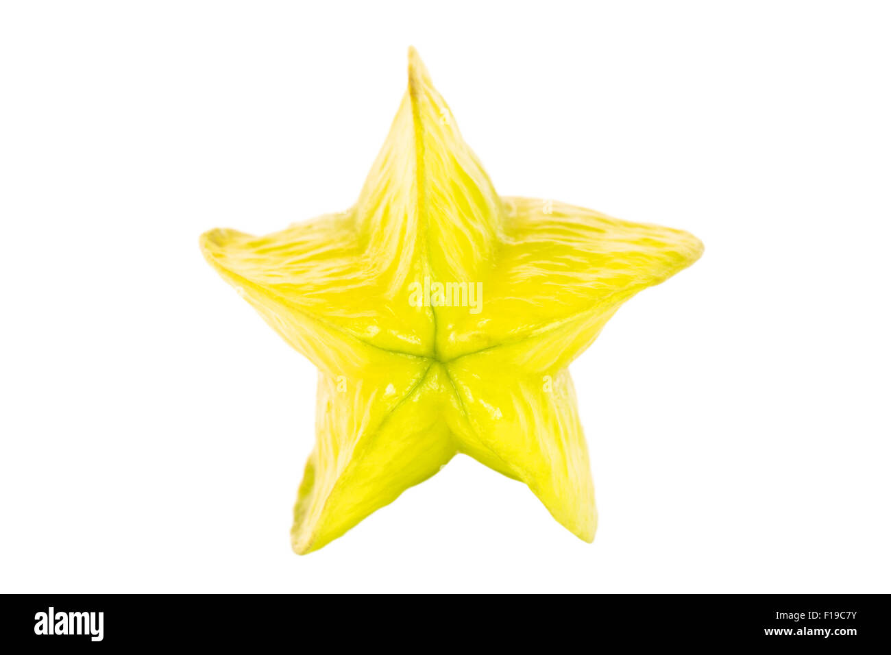 Close-up of a whole ripe carambola (starfruit), viewed from the front, isolated on white background. - Stock Image