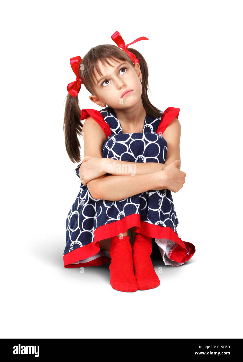 Sitting sad, thoughtful child girl with red bows, on white - Stock Image