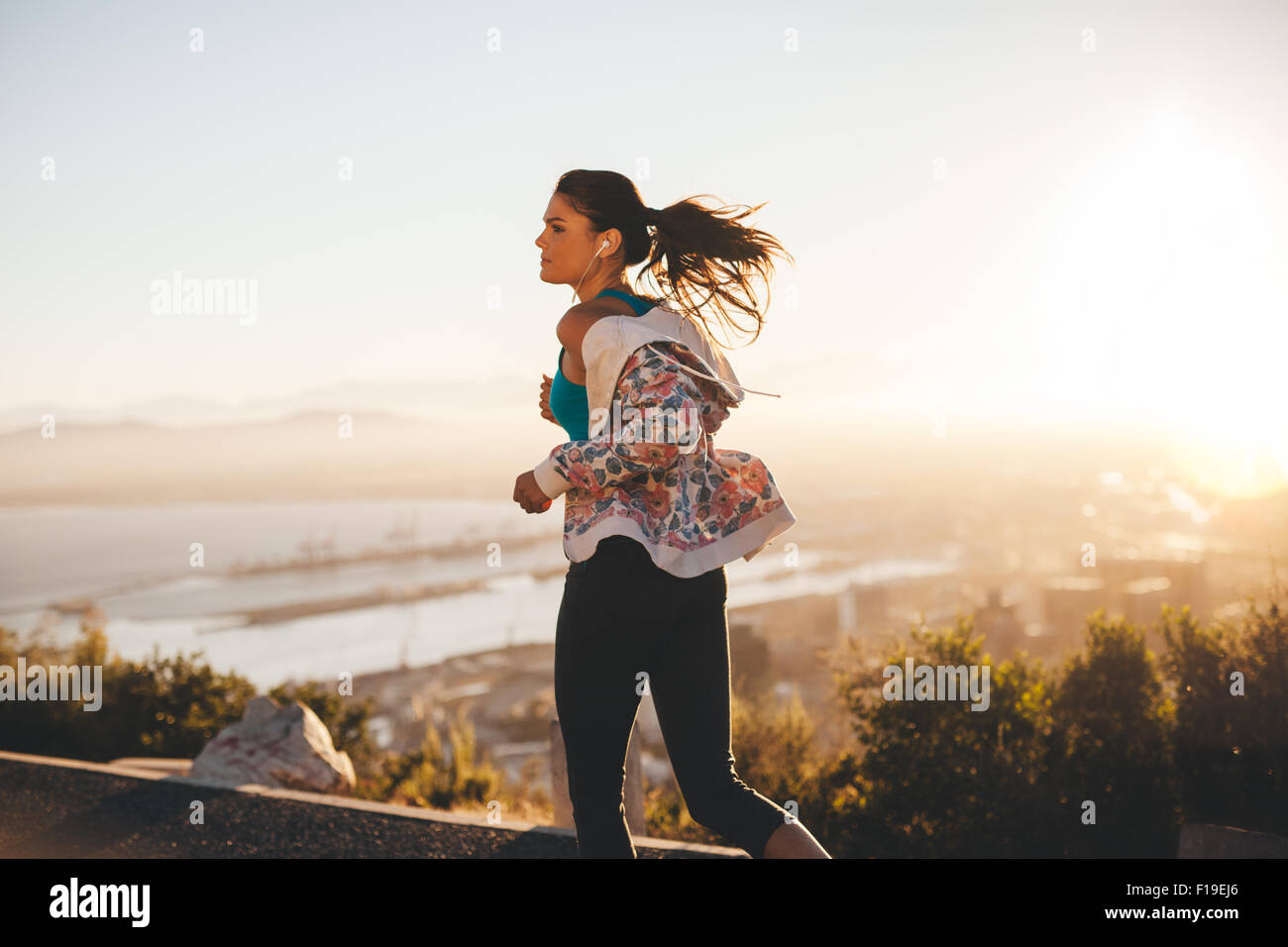 Outdoor shot of a young woman on her morning run. Fitness woman running on country road. - Stock Image