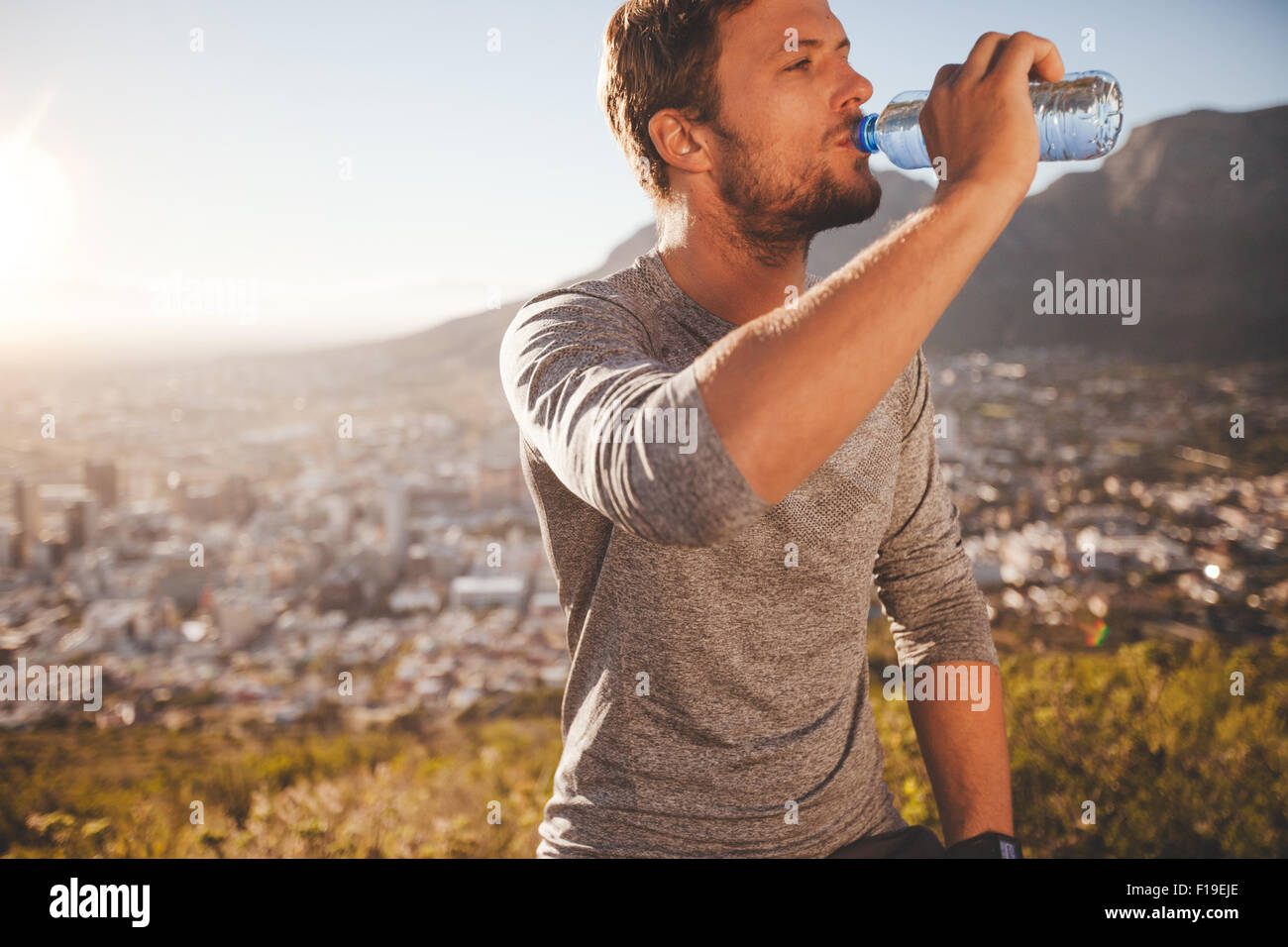 Young runner taking a break after morning run drinking water. Young man relaxing after a running training session Stock Photo