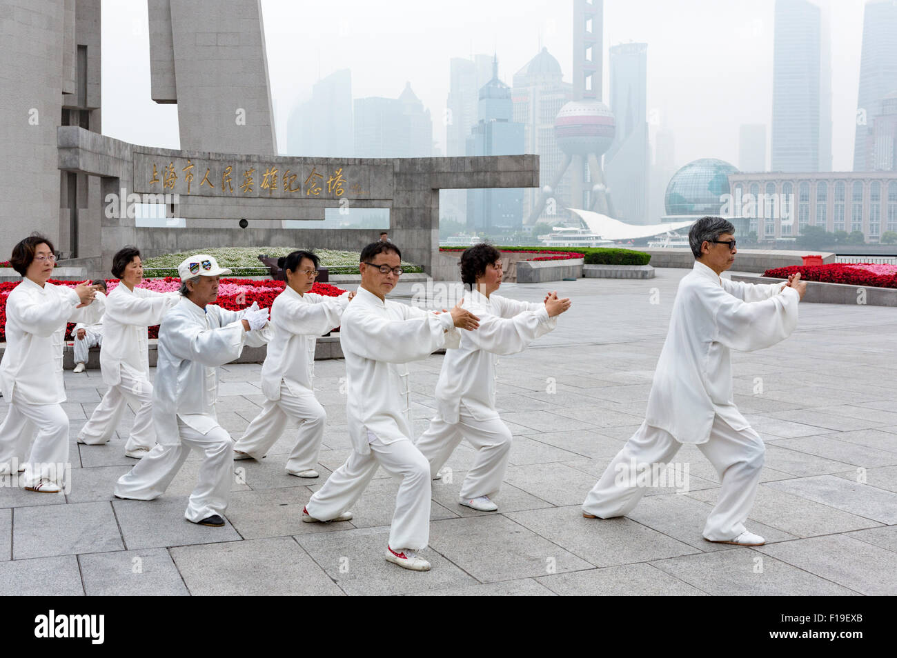Tai Chi group in matching gear exercises near Shanghai's Bund in view of the Pudong skyline, which is obscured - Stock Image
