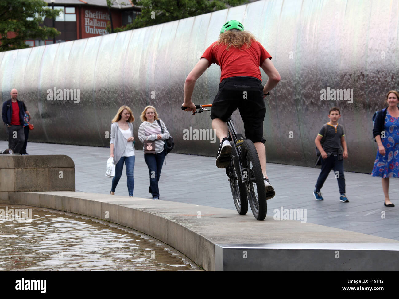 Stunt cyclist at the Cutting Edge steel sculpture and  water feature outside Sheffield Railway Station - Stock Image