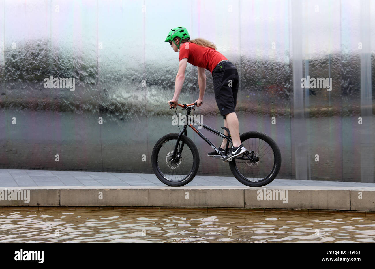 Stunt cyclist at the Cutting Edge steel sculpture and  water feature at Sheffield Railway Station - Stock Image