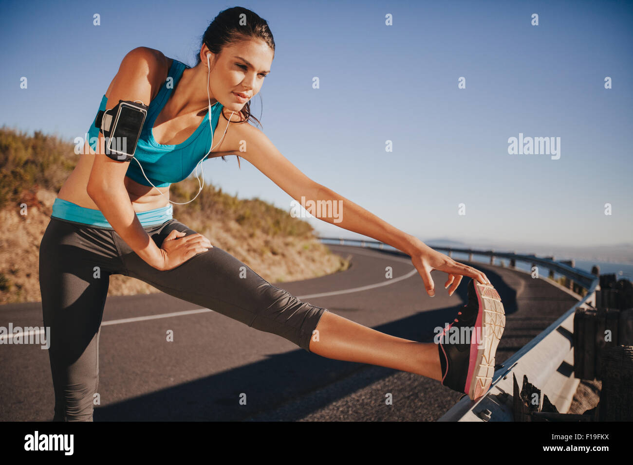 Determined young woman warming up before a run. Female athlete stretching her leg on road guardrail in morning. - Stock Image