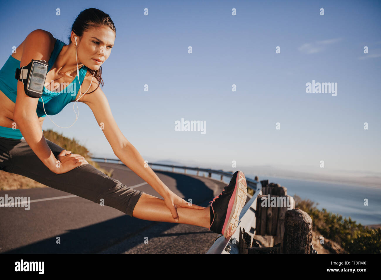 Outdoor shot of woman stretching her legs before a run. Determined runner preparing for outdoor training looking - Stock Image