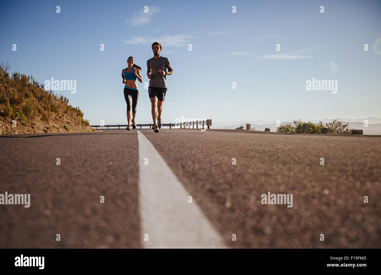 Two young people running on country road, low angle shot of runners on open road on  a summer day. - Stock Image