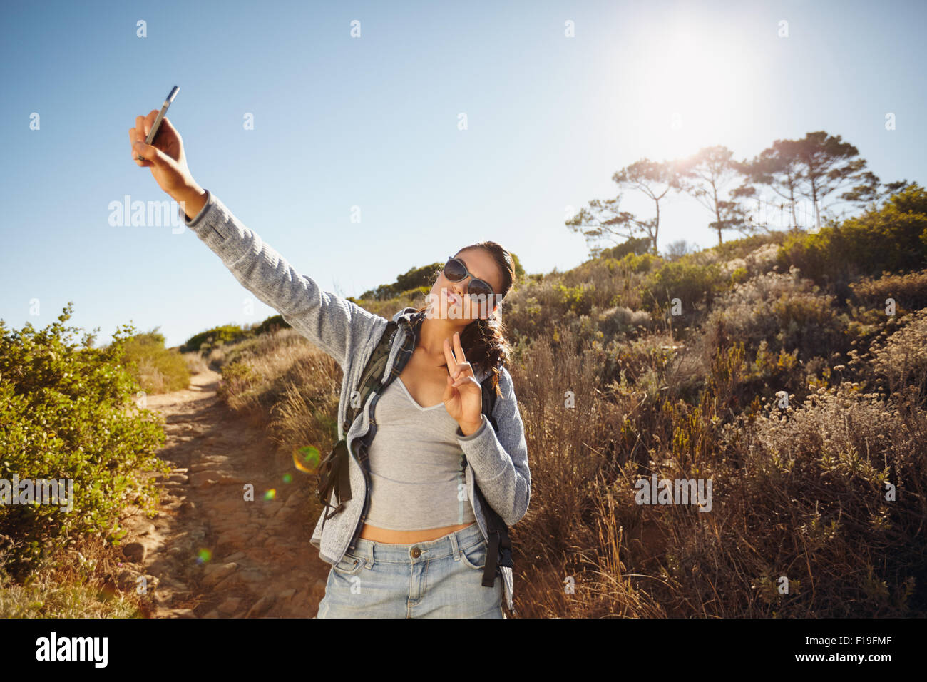 Happy and energetic young woman taking a selfie. She is holding the mobile phone camera high posing and gesturing - Stock Image