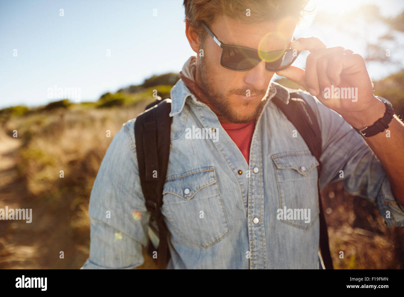 Close up shot of young man on country hike. Caucasian male model hiking wearing sunglasses with sun flare. - Stock Image