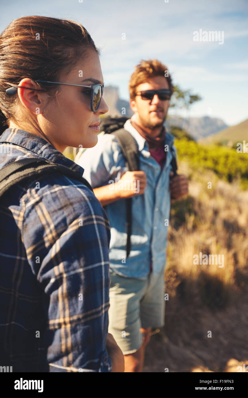 Couple on hike in countryside. Woman standing in front looking at a view with man in background. Caucasian couple - Stock Image