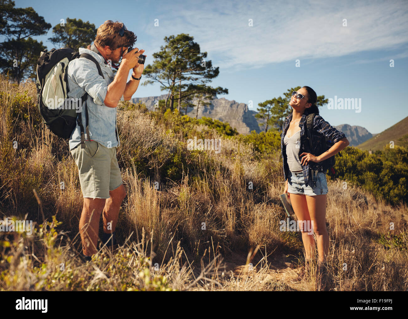 Outdoor shot of tourist couple hiking and taking photos with camera. Man taking picture of girlfriend in countryside. - Stock Image