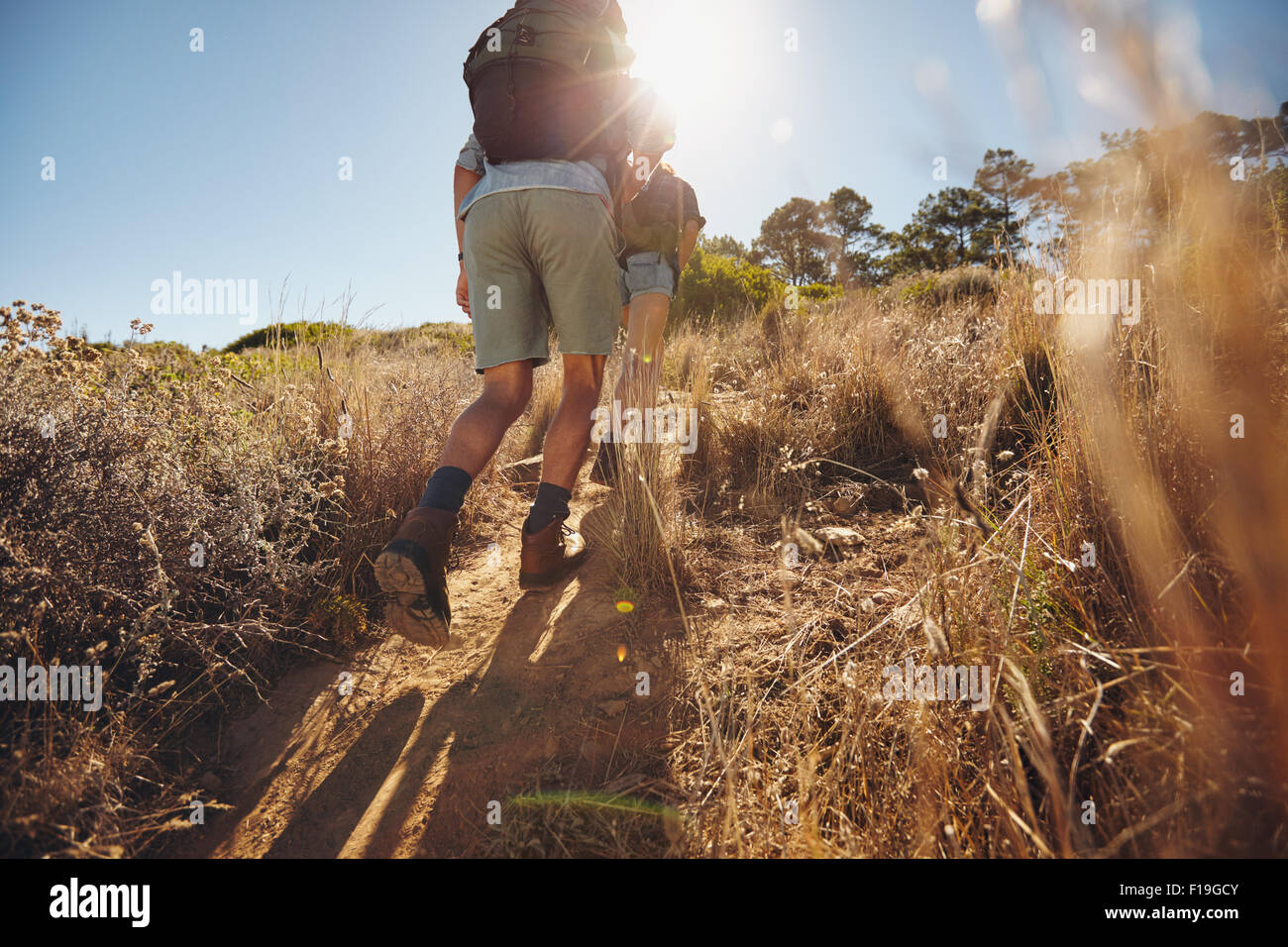 Low angle view of two young people climbing uphill on a mountain. Couple on a hiking trip on a sunny day. - Stock Image