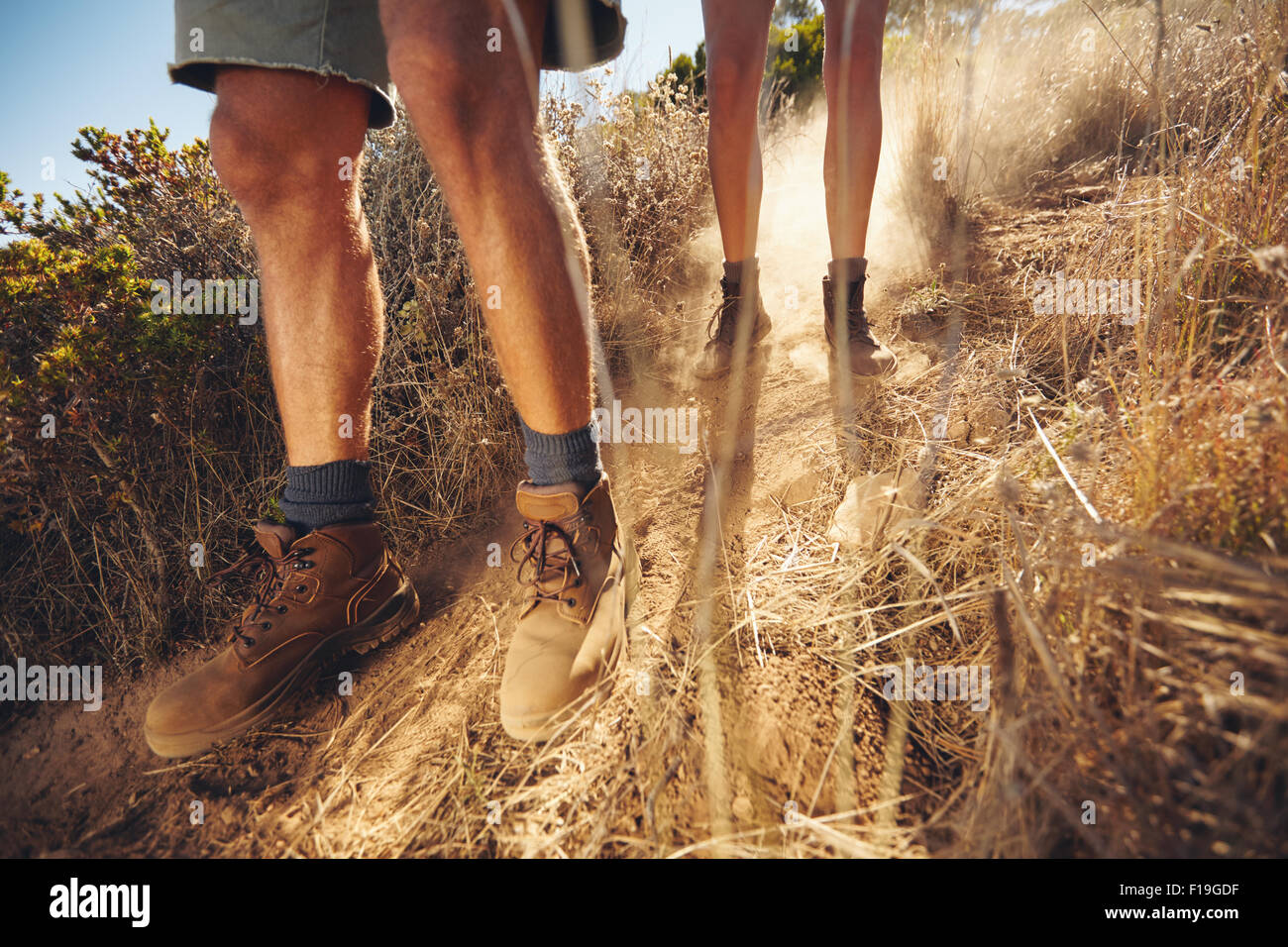 Low angle view of young people walking on mountain trail. Couple hiking on dirt path coming downhill. Cropped shot - Stock Image