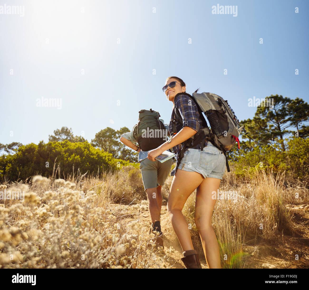 Young people doing a uphill climb while hiking in countryside. Woman with map looking back over her shoulder smiling - Stock Image
