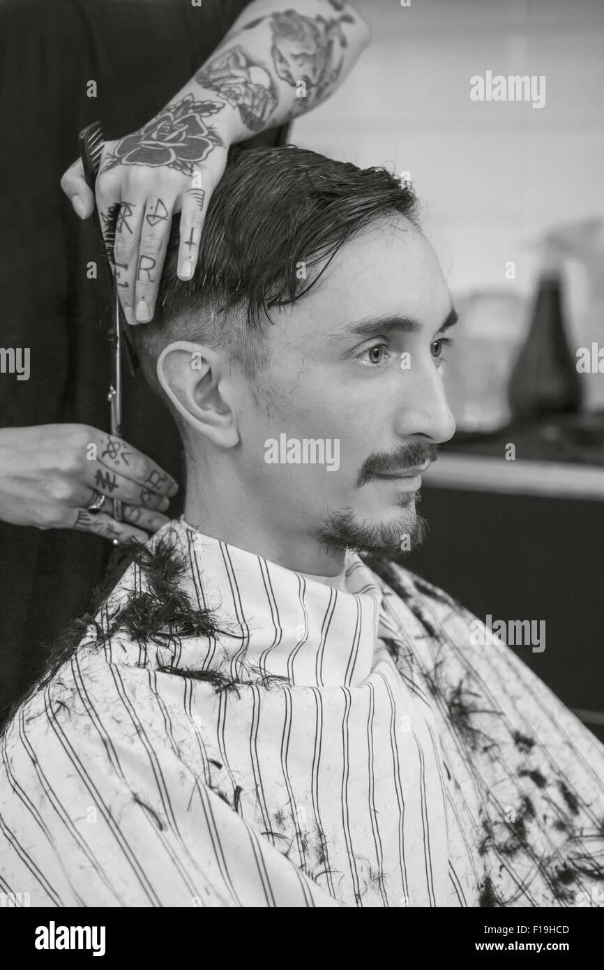 man getting a haircut at a barber shop - Stock Image